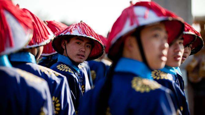 Chinese actors dressed as Qing Dynasty servants take part in a rehearsal of ancient Qing Dynasty ceremony for the upcoming Chinese New Year at Ditan Park in Beijing, Friday, Feb. 8, 2013. Chinese will celebrate the Lunar New Year on Feb. 10 this year which marks the Year of Snake. (AP Photo/Andy Wong)