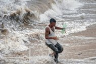 A man runs away from the waves in Gibara, Holguin province, Cuba on August 25, during tropical storm Isaac. The strengthening storm is barreling toward Florida and is predicted to become a hurricane on Sunday, forcing a one-day delay to the main events of the Republican convention, after leaving four people dead in Haiti