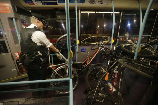 An officer loads arrested cyclist's bicycles after a Critical Mass bike protest outside the Olympic Park during the 2012 Summer Olympics Opening Ceremony, Friday, July 27, 2012, in London. (AP Photo/M