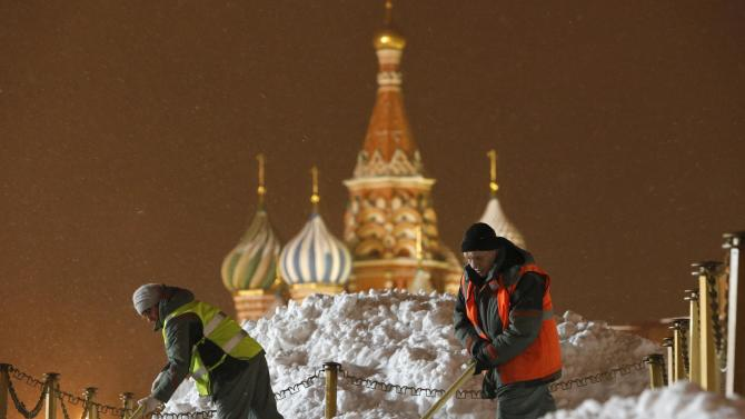 Workers clear and remove snow in Red Square in central Moscow