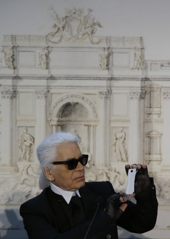 "Designer Karl Lagerfeld takes a picture with his mobile phone backdropped by a drawing of Trevi's fountain during a press conference, in Rome, Monday, Jan. 28, 2013. The Fendi fashion house is financing an euro 2.12 million ($2.8 million) restoration of Trevi Fountain in Rome, famed as a setting for the film ""La Dolce Vita'' and the place where dreamers leave their coins. The 20-month project on one of the city's most iconic fountains was being unveiled at a city hall press conference Monday. (AP Photo/Gregorio Borgia)"