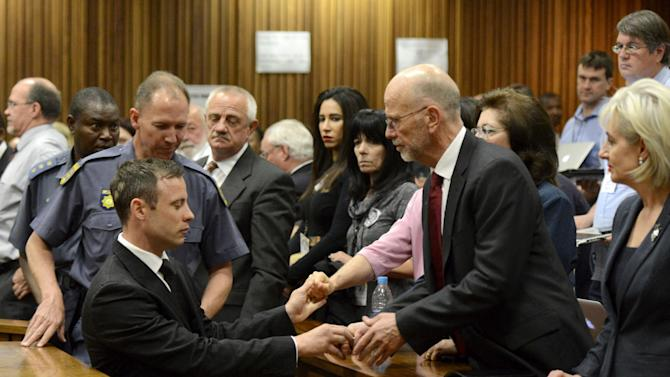Oscar Pistorius, front left, greets his uncle Arnold Pistorius, right, and other family members as he is led out of court in Pretoria, South Africa, Tuesday, Oct. 21, 2014. Pistorius received a five-year prison sentence for culpable homicide by judge Thokozile Masipais for the killing of his girlfriend Reeva Steenkamp last year (AP Photo/Herman Verwey, Pool)