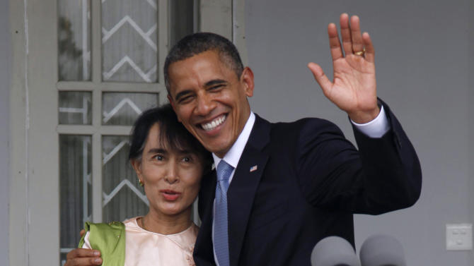 FILE - In this Nov. 19, 2012 file photo, U.S. President Barack Obama waves to the media as he embraces Myanmar opposition leader Aung San Suu Kyi after they spoke to the media at her residence in Yangon, Myanmar, Monday. The United States is unwinding two decades of sanctions against Myanmar, as the country's reformist leadership oversees rapid-fire economic and political change. Obama's visit this week, the first by a serving U.S. president, is a sign of how far relations have come. But Washington continues to take a calibrated approach to easing sanctions, keen to retain leverage should Myanmar's reform momentum stall. (AP Photo/Khin Maung Win, Pool, File)