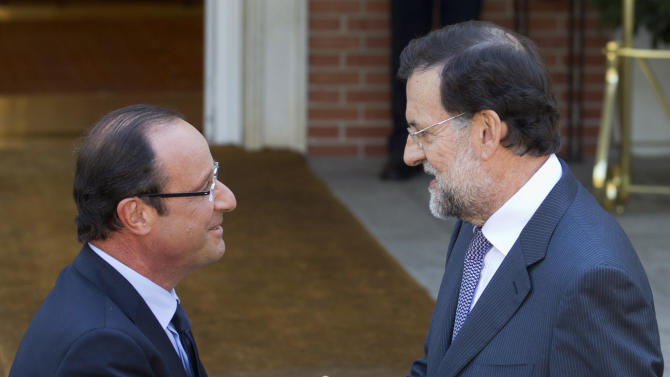 French President Francois Hollande, left, is greeted by Spain's Prime Minister Mariano Rajoy at the Moncloa Palace in Madrid Thursday Aug. 30, 2012.  Hollande met Rajoy for talks on Spain's economic crisis and the future of the euro. (AP Photo/Paul White)
