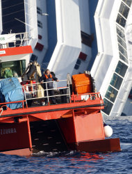 A skimmer boat collects waste around the grounded cruise ship Costa Concordia off the Tuscan island of Giglio, Italy, Monday, Jan. 30, 2012. Residents of Giglio are growing increasingly worried about threats to the environment and the future of the Italian island as bad weather again forced suspension of the recovery operation of the capsized cruise ship Costa Concordia. (AP Photo/Pier Paolo Cito)
