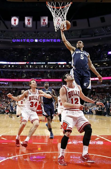 Memphis Grizzlies' Courtney Lee (5) scores over Chicago Bulls' Kirk Hinrich (12) and past Mike Dunleavy (34) during the second half of an NBA basketball game on Friday, March 7, 2014, in Chica