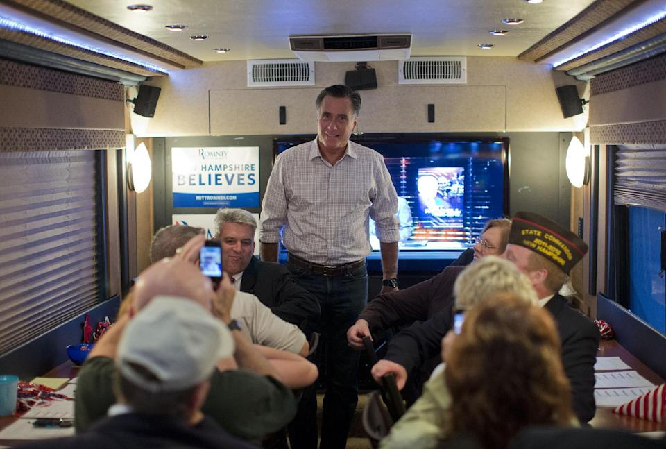 "Republican presidential candidate, former Massachusetts Gov. Mitt Romney speaks with members of the ""New Hampshire Veterans and Military Families for Mitt"" on a campaign bus, Thursday, Sept. 6, 2012, in Concord, N.H.  (AP Photo/Evan Vucci)"