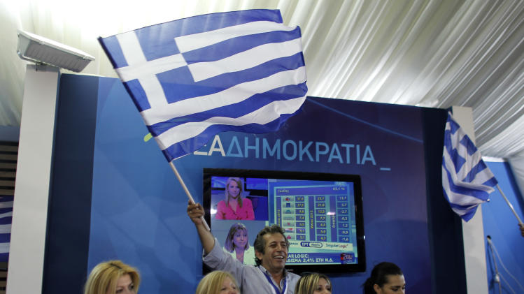 Supporters of the New Democracy conservative party celebrate at an election kiosk  at Syntagma square in Athens, Sunday, June 17, 2012. The pro-bailout New Democracy party came in first Sunday in Greece's national election, and its leader has proposed forming a pro-euro coalition government.(AP Photo/Kostas Tsironis)
