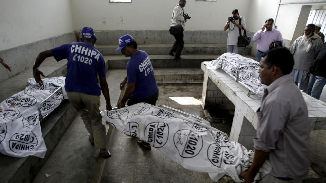 Pakistani rescue workers carry the dead body of a female polio worker, killed by unknown gunmen, at the morgue of local hospital in Karachi, Pakistan, Tuesday, Dec. 18, 2012. Gunmen killed several people working on a government polio vaccination campaign in two different Pakistani cities on Tuesday, officials said. The attacks were likely an attempt by the Taliban to counter an initiative the militant group has long opposed. (AP Photo/Fareed Khan)