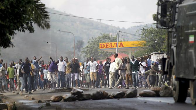 Protesters throw stones to a water cannon during clashes with riot police in Burundi's capital Bujumbura