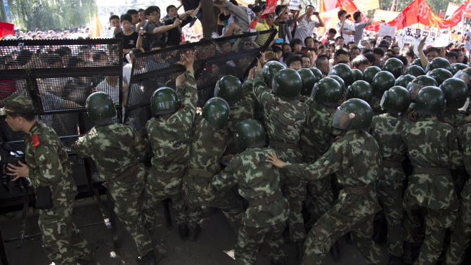 Chinese Paramilitary Policemen try to block demonstrators break through the fence set up outside the Japanese Embassy during an anti-Japan protest in Beijing Saturday, Sept. 15, 2012. Tensions between the two countries flared anew after the Japanese government bought the disputed islands from their private Japanese owners this week. The uninhabited islands, Senkaku in Japan and Diaoyu in China, claimed by both countries as well as Taiwan, have become a rallying point for nationalists on both sides. (AP Photo/Andy Wong)