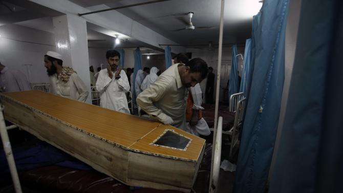 People stand near coffin of a victim, who was killed in a bomb blast, at a hospital in Peshawar