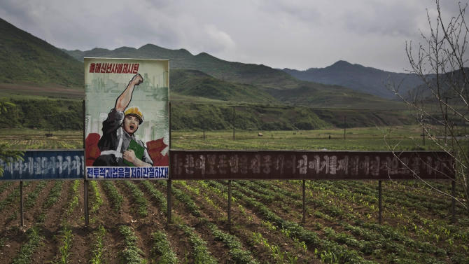 """In this Monday, June 16, 2014 photo, a propaganda billboard stands in a field south of Samsu, in North Korea's Ryanggang province. The sign reads: """"Let's complete the tasks set forth in the New Year's address."""" (AP Photo/David Guttenfelder)"""