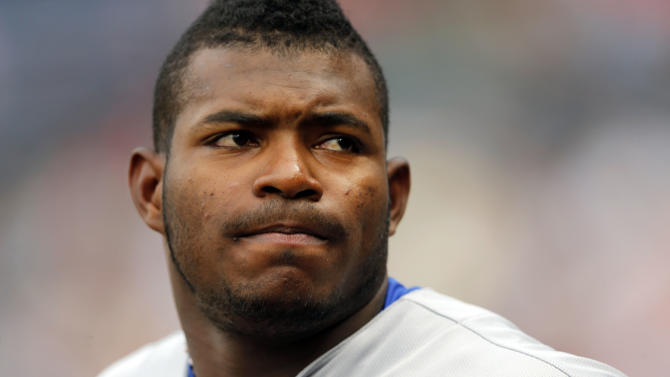 File-This July 20, 2015, file photo shows Los Angeles Dodgers right fielder Yasiel Puig looking on from the dugout during a baseball game against the Atlanta Braves in Atlanta.  Puig suffered a swollen eye and facial bruises during a fight with a bouncer. Miami police spokesman Major Delrish Moss says the injuries happened Wednesday night as the Cuban player was leaving the Blue Martini bar at bouncers' request following an argument with his sister. (AP Photo/John Bazemore, File)