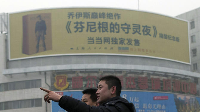 "A Chinese man points near a large billboard advertising the translated work of James Joyce's ""Finnegans Wake"" on a street in Beijing, China, Wednesday, Jan. 30, 2013. The Chinese version is no easier to read than the original, the loyal-minded translator assures, but James Joyce's ""Finnegans Wake"" has still sold out its initial run in China — with the help of some big urban billboards. The book, widely considered Joyce's most experimental and inscrutable work, was promoted by an unusual billboard campaign in major Chinese cities — with 16 of them in Shanghai alone. The official Xinhua News agency said it was the first time a book had been promoted that way in China. (AP Photo/Ng Han Guan)"