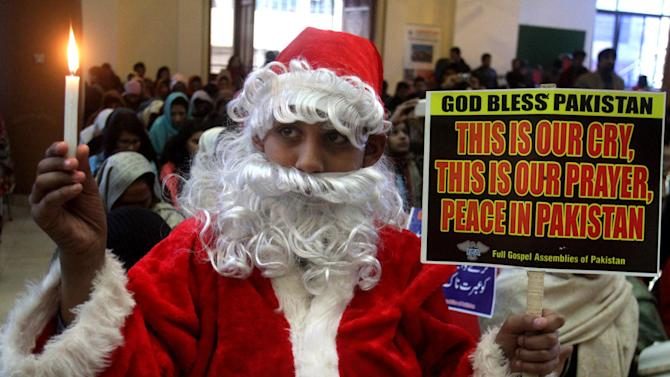 A Pakistani Christian boy dresses as Santa Claus as he takes part in a special prayer for victims killed in last Tuesday's Taliban attack on a military-run school, in Lahore, Pakistan, Sunday, Dec. 21, 2014. The attack in Peshawar shocked the nation and prompted a massive military response in the tribal regions along the Afghan border, longtime strongholds of both foreign and local militants. (AP Photo/K.M. Chaudary)