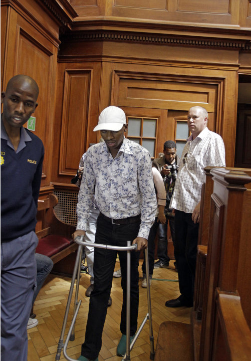Xolile Mngeni with his walking frame as he approaches the dock, in a courtroom, in  Cape Town, South Africa, Monday, Nov. 19, 2012, as he awaits the court's verdict. Mngeni,was arrested for the killin