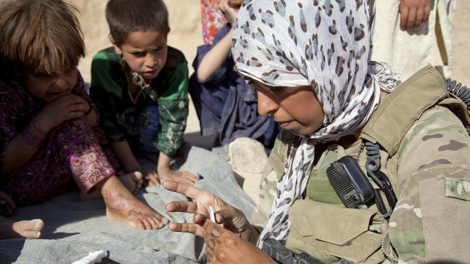 In this image released by the Defense Department, a member of the U.S. Army Cultural Support Team, attached to Special Operations Task Force - South, applies medicine to the burn wound of a child in a northern Khakrez District village, June 28, 2011, in Kandahar province, Afghanistan. (AP Photo/Department of Defense, Pfc. Kaimana-Ipulani Kalauli-Mendoza)