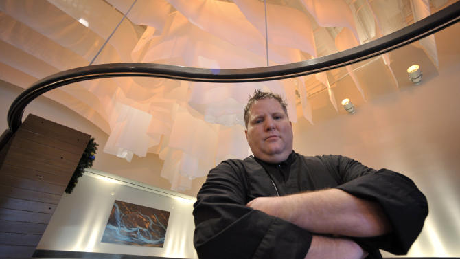In this photo made Dec. 22, 2011, Brandt Evans poses in the dining room of his Pura Vida restaurant in downtown Cleveland. Evens expects the opening of the nearby casino in March will boost his business, necessitating the hiring of an additional 15-20 employees. (AP Photo/Mark Duncan)