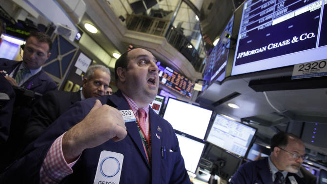 Specialist Peter Giacchi, center, calls out prices as he works at the post that handles JP Morgan on the floor of the New York Stock Exchange, Friday, May 11, 2012. Financial stocks are leading the market lower in early trading after JPMorgan disclosed a huge trading loss.(AP Photo/Richard Drew)