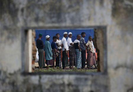 Rohingya migrants who arrived in Indonesia last week by boat are seen through the window of an abandoned building as they wait in line for breakfast at a temporary shelter in Aceh Timur regency near Langsa in Indonesia's Aceh Province