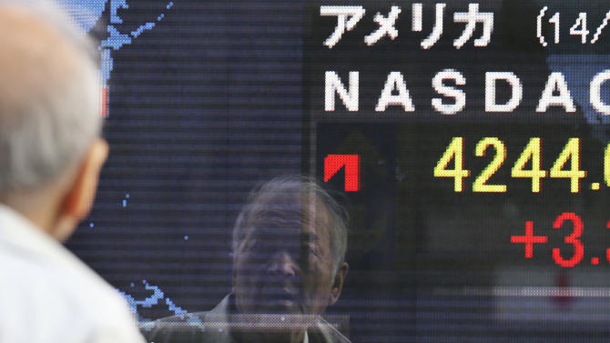 A man reflected on the electronic board of a securities firm in Tokyo,Tuesday, Feb. 18, 2014. Japan led Asian stock markets higher Tuesday after the country's central bank announced new measures to support growth.(AP Photo/Koji Sasahara)
