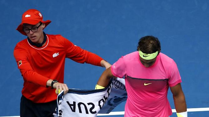 Rafael Nadal of Spain takes a towel from a ball kid as he plays Tomas Berdych of the Czech Republic during their quarterfinal match at the Australian Open tennis championship in Melbourne, Australia, Tuesday, Jan. 27, 2015. (AP Photo/Vincent Thian)