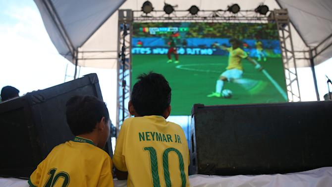 A couple of young soccer fans, watch on a giant screen television Brazil play Cameroon in the soccer World Cup match, in Manaus, Brazil, Monday, June 23, 2014. Brazil's Neymar scored twice in the first half to lead Brazil to a 4-1 win over Cameroon on Monday, helping the hosts secure a spot in the second round of the soccer World Cup. (AP Photo/Martin Mejia)