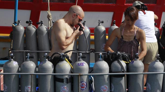 Tourists check their oxygen tanks before diving on the island of Koh Tao