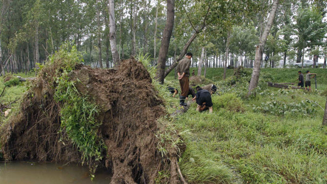 People prepare to remove fallen trees on Wednesday, Aug. 29, 2012 in Pyongyang's Sunan District in North Korea after a typhoon hit the area. A second typhoon in less than a week is approaching North Korea, threatening more rain in a country where storms often mean catastrophe because of deforestation and fragile infrastructure.  (AP Photo/Kim Kwang Hyon)