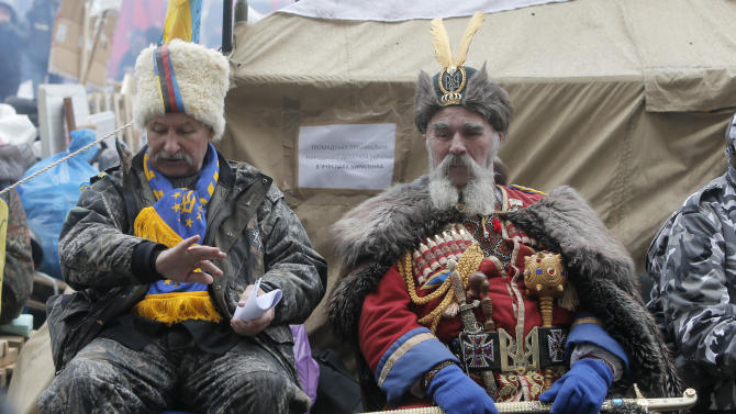 An Pro-European Union supporter dressed as Cossack has a rest at a tent camp in the city main street of Khreschatyk in Kiev Ukraine, Monday, Dec. 16, 2013. Ukraine's opposition appears confident and shows no sign of relenting in its standoff with the government. The government has made some gestures toward the opposition, rejected some of its main demands and is opaque on another. (AP Photo/Efrem Lukatsky)