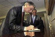 British Defense Secretary Phillip Hammond signs a guestbook as he is welcomed to the Pentagon by U.S. Secretary of Defense Leon E. Panetta (R) in Washington, July 18, 2012. REUTERS/Glenn Fawcett/Handout