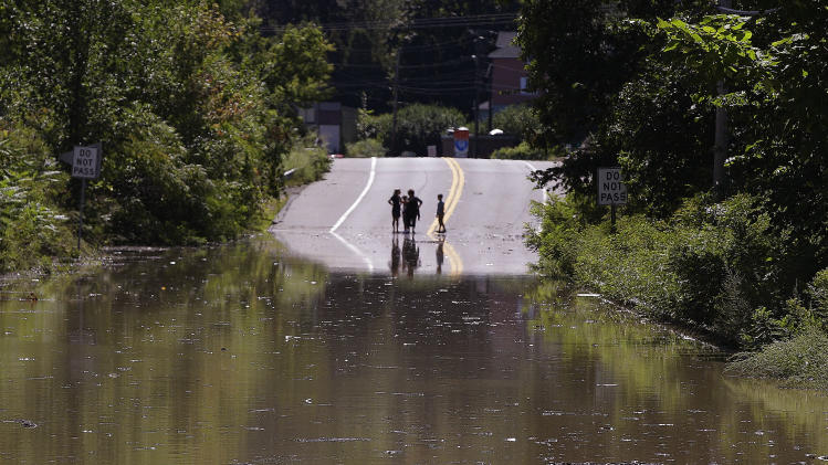 Children stand on the far side of a flooded portion of Massachusetts Rt. 5 which is closed to traffic in Northhampton, Mass., Monday afternoon, Aug. 29, 2011 due to flooding from tropical storm Irene.  (AP Photo/Stephan Savoia)