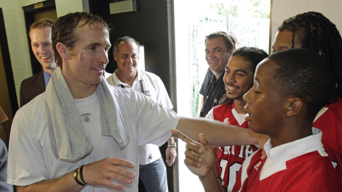 FILE - This Sept. 16, 2010 file photo shows New Orleans Saints quarterback Drew Brees talking with high school football players at the NFL football team's training facility in Metairie, La. Brees knows he has a dangerous job. The record-setting quarterback of the New Orleans Saints is eager to make football safer at all levels. So he's teamed up with PACE (Protecting Athletes Through Concussion Education), a program that provides free concussion testing for more than 3,300 middle and high schools and youth sports organizations.  (AP Photo/Bill Haber, File)