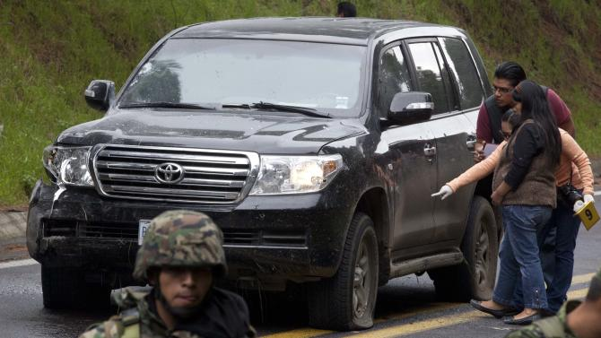 An armored U.S. Embassy vehicle attacked by unknown assailants on the highway leading to the city of Cuernavaca, is checked by security personal near Tres Marias, Mexico, Friday, Aug. 24, 2012. Two U.S. government employees were shot and wounded in an attack on their vehicle south of Mexico City on Friday, a law enforcement official said. (AP Photo/Alexandre Meneghini)