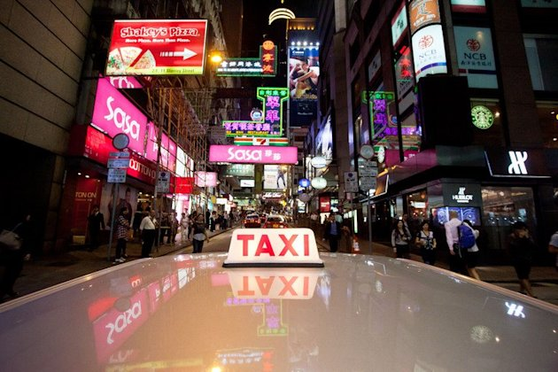 A taxi drives through the Central district of Hong Kong on November 19, 2011. A taxi driver who endured a six-month lawsuit after overcharging a passenger by six US cents has finally had his name cleared by a Hong Kong court