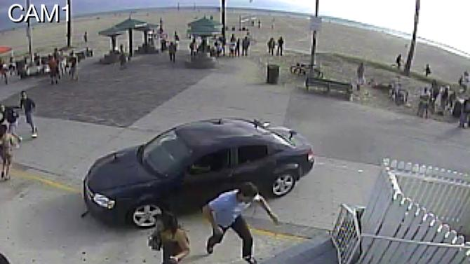 In this image take from a security camera, pedestrians scatter as a car drives through a packed afternoon crowd along the Venice Beach boardwalk in Los Angeles, Saturday, Aug. 3, 2013. At least a dozen people were injured, two of them critically, according to police. (AP Photo/Snapchat)