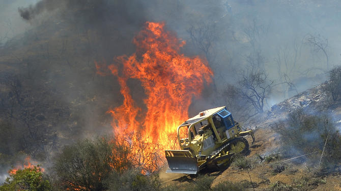 A bulldozer clears a firebreak near a wildfire burning along a hillside near homes in Thousand Oaks, Calif., Thursday, May 2, 2013. A Ventura County Fire Department spokeswoman said the blaze that broke out Thursday morning near Camarillo and Thousand Oaks, 50 miles west of Los Angeles, had spread to over 6,500 acres, forcing evacuations of nearby neighborhoods. (AP Photo/Mark J. Terrill)