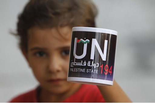 A Palestinian boy holds a coffee mug in Gaza City