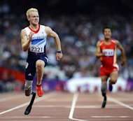 Britain's Jonnie Peacock (L) powers home to win the men's 100m T44 heat 1 during the athletics competition at the London 2012 Paralympic Games at the Olympic Stadium in east London