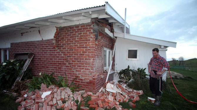 Kieran Hickman surveys the damage to his property at Taimate, New Zealand Friday, Aug. 16, 2013, after a 6.5 magnitude trembler. Strong earthquakes shook central New Zealand on Friday, damaging homes and roads and sending office workers scrambling for cover in the capital. No serious injuries were reported. (AP Photo/NZ Herald, Tim Cuff) NEW ZEALAND OUT, AUTSRALIA OUT