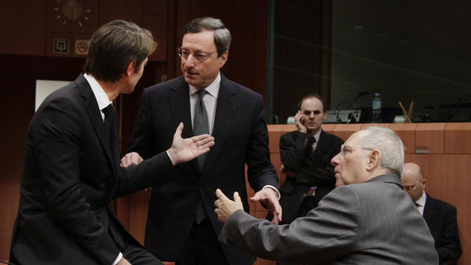 German Finance Minister Wolfgang Schaeuble, right, speaks with European Central Bank President Mario Draghi, center, and French Finance Minister Francois Baroin, left, during a round table meeting of the eurogroup at the EU Council building in Brussels on Tuesday, Nov. 29, 2011. The 17 finance ministers of countries that use the euro converged on EU headquarters Tuesday in a desperate bid to save their currency and to protect Europe, the United States, Asia and the rest of the global economy from a debt-induced financial tsunami. (AP Photo/Virginia Mayo)