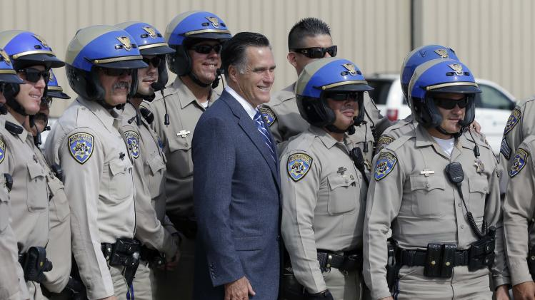 Republican presidential candidate and former Massachusetts Gov. Mitt Romney poses for a picture with members of the California Highway Patrol before he boards his campaign plane in San Diego, Saturday, Sept. 22, 2012. (AP Photo/Charles Dharapak)