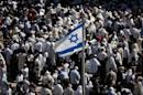 An Israeli flag flutters as Jewish men draped in prayer shawls perform the Cohanim prayer (priest's blessing) during the Pesach (Passover) holiday at the Western Wall in the Old City of Jerusalem on April 6, 2015