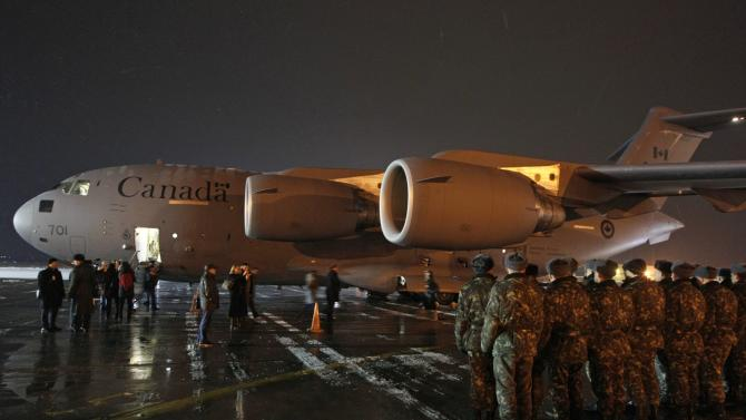 Ukrainian servicemen line up near a transport plane which delivered the freight from Canada at Boryspil International airport outside Kiev