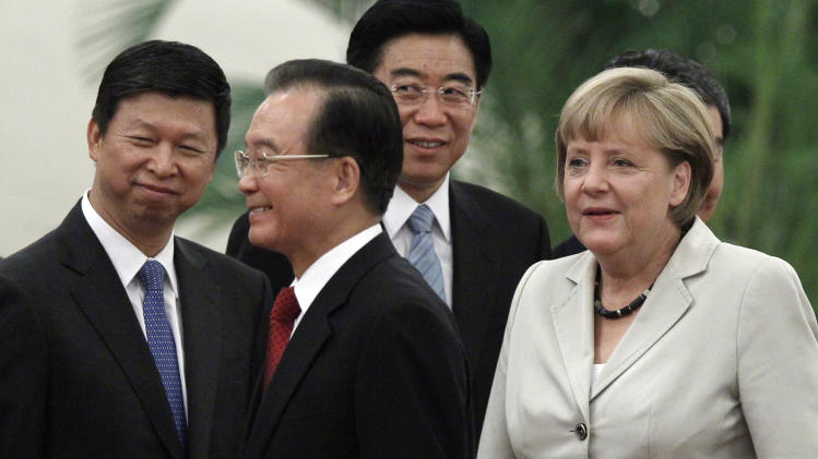 German Chancellor Angela Merkel, right, and Chinese Premier Wen Jiabao, second from left, walk past Chinese officials during a welcome ceremony at the Great hall of the People in Beijing, Thursday, Aug. 30, 2012. (AP Photo/Ng Han Guan)