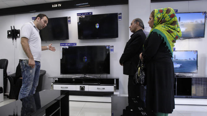 In this picture taken on Thursday, Aug. 16, 2012, an Iranian shopkeeper, left, explains about TV sets for his customers, in an electronics market in Tehran, Iran. While Iran's mainstay oil exports remains the centerpiece of Western sanctions _ intended to wring concessions on Iran's nuclear program and ease Israeli threats of a military strike _ the Islamic Republic hangs on as OPEC's third-largest exporter as it feeds the hungry energy markets in China, India and across Asia. But less noted _ but potentially more unsettling to Iran's leaders in the coming months _ is the increasing pinch on the workaday economy: The commerce, transactions and trading that provide the paychecks and economic lifelines for millions of people. (AP Photo/Vahid Salemi)