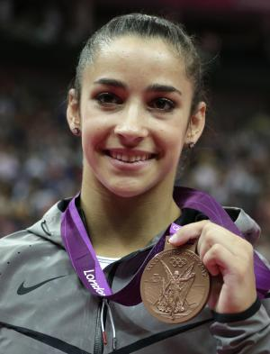 U.S. gymnast Alexandra Raisman displays her bronze medal for the balance beam during the artistic gymnastics women's apparatus finals at the 2012 Summer Olympics, Tuesday, Aug. 7, 2012, in London. (AP Photo/Gregory Bull)