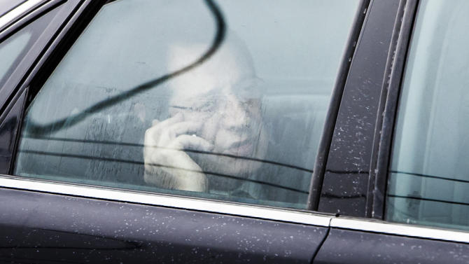 Cypriot President Nicos Anastasiades speaks on his phone in his car as he arrives at the airport in Brussels on Sunday, March 24, 2013. The EU says a top official will chair a high-level meeting on Cyprus in a last-ditch effort to seal a deal before finance ministers decide whether the island nation gets a 10 billion euro bailout loan to save it from bankruptcy. (AP Photo/Geert Vanden Wijngaert)