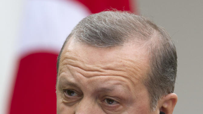 Turkish Prime Minister Recep Tayyip Erdogan speaks while removing a translation earphone during a news conference with President Barack Obama in the Rose Garden of the White House in Washington, Thursday, May 16, 2013. (AP Photo/Jacquelyn Martin)